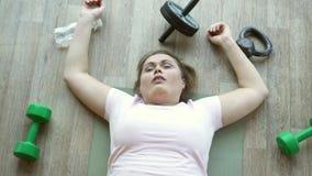 在健身房锻炼的地板上用尽的肥胖妇女说谎 影视素材
