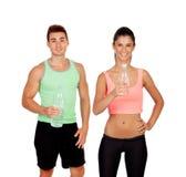 在健身房饮用水的年轻夫妇 免版税库存照片