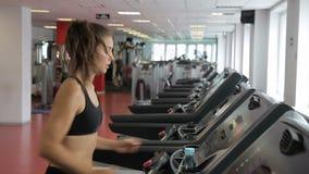 在健身房,一名苗条妇女沿踏车跑 影视素材