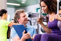 在健身房-黑人妇女和个人教练员的健身训练 免版税图库摄影