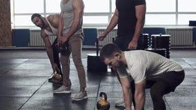 在健身房-在锻炼期间的男性朋友的力量训练 股票录像
