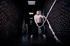 在健身房锻炼英俊的俊男完成的健身锻炼的健身作战的绳索 在健身房锻炼的Crossfit作战的绳索 库存照片