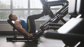 在健身房-行使在腿新闻机器的肌肉人 图库摄影