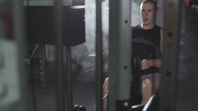 在健身机器的人锻炼在与拷贝空间的黑暗的健身房在左边 股票录像