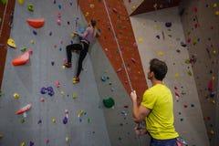 在健身演播室供以人员拿着看运动员上升的墙壁的绳索 免版税库存照片