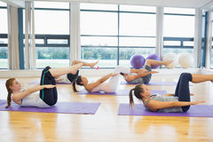 在健身演播室把舒展在席子分类在瑜伽类 免版税库存照片
