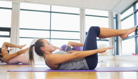 在健身演播室把舒展在席子分类在瑜伽类 免版税库存图片