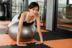 在健身球的亚洲美丽的妇女板条 库存照片