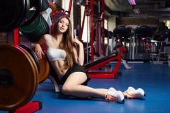 在健身锻炼期间的美好的有吸引力的女性肉欲的女孩作为呼吸在健身房 免版税图库摄影