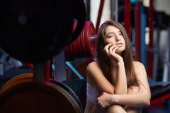在健身锻炼期间的美好的有吸引力的女性肉欲的女孩作为呼吸在健身房 免版税库存图片
