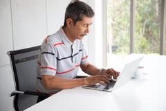 在偶然工作的资深亚洲商人在用途膝上型计算机旁边 免版税图库摄影