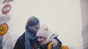 在偶然温暖的衣裳的愉快的轻松的年轻浪漫夫妇在一多雪的冬天圣诞节一起走,拥抱并且亲吻 股票视频