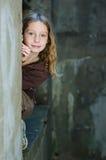 在偷看非离子活性剂墙壁的女孩附近 库存照片