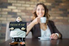 在储备标志前面的美丽的少妇饮用的咖啡 库存照片