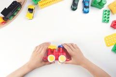 在儿童使用与玩具火车和许多玩具的` s手上的顶视图在白色桌背景 免版税库存照片