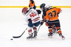 在儿童冰曲棍球队之间的比赛 免版税图库摄影