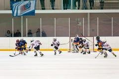 在儿童冰曲棍球队之间的比赛 库存照片