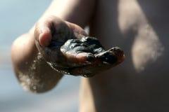 在儿童右手的黑湿沙子 库存图片