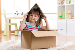 在儿童居室哄骗使用在一个玩具房子里的女孩 库存照片
