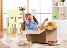 在儿童居室哄骗演奏试验飞行一个纸板箱 免版税库存图片