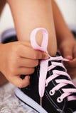 在儿童手上的特写镜头,他们栓鞋子浅景深 免版税库存图片