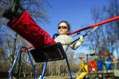 在儿童操场的逗人喜爱的小女孩摇摆的跷跷板 图库摄影