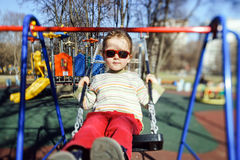 在儿童操场的逗人喜爱的小女孩摇摆的跷跷板 免版税图库摄影