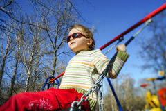 在儿童操场的逗人喜爱的小女孩摇摆的跷跷板 免版税库存图片