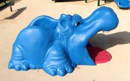在儿童的游乐场的五颜六色的蓝色和红色河马玩具 免版税库存照片