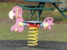在儿童的游乐场的红色春天车手 免版税库存图片
