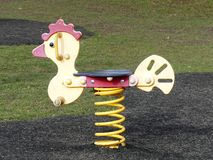 在儿童的游乐场的黄色春天车手 免版税库存照片