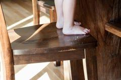 在儿童的脚旁边的面包屑在餐厅椅子 库存图片