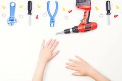 在儿童` s手上的顶视图有在白色背景的五颜六色的玩具工具的 库存照片