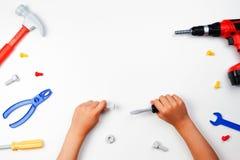 在儿童` s手上的顶视图有在白色背景的五颜六色的玩具工具的 图库摄影