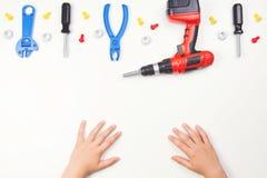 在儿童` s手上的顶视图有在白色背景的五颜六色的玩具工具的 库存图片