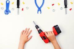 在儿童` s手上的顶视图有在白色背景的五颜六色的玩具工具的 免版税图库摄影