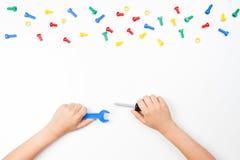 在儿童` s的顶视图递使用与在白色背景的五颜六色的玩具工具 免版税库存照片