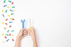 在儿童` s的顶视图递使用与在白色背景的五颜六色的玩具工具 免版税库存图片