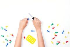 在儿童` s的顶视图递使用与在白色背景的五颜六色的玩具工具 库存图片