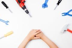 在儿童` s的顶视图递使用与在白色背景的五颜六色的玩具工具 免版税图库摄影