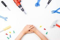 在儿童` s的顶视图递使用与在白色背景的五颜六色的玩具工具 库存照片