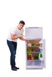 在充分冰箱的人食物旁边 免版税库存照片