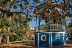 在充分庭院的老五颜六色的眺望台树中间,在São曼纽尔的一个晴天 库存照片