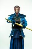 在充分的装甲的Kendo - Kendoka有shinai的,在白色背景射击的演播室 库存照片