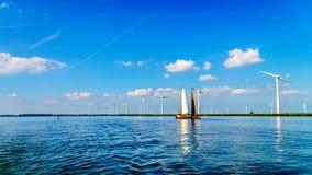 在充分的风帆的两条历史的木Botter小船在沿Veluwemeer岸的一个风力场附近  库存照片