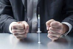 在充分针的紧张的商人疫苗或药物前面 库存照片
