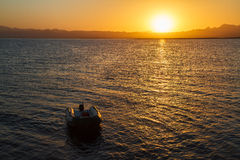 在充气救生艇的日落 库存照片