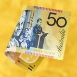 在充满活力的金黄背景的澳大利亚金钱 免版税库存图片