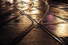 在光和街道的湿台车railes 免版税库存照片