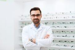 在光学商店供以人员玻璃和外套的眼镜师 库存照片
